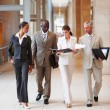 Sophisticated team of business walking through the hallwa - Stock Photo