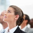 A beautiful young business woman looking upwards - Stock Photo
