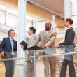 Royalty-Free Stock Photo: Successful business group standing by a glass railing