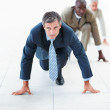 Mature business man in position for a race, against colleagues - Stock Photo