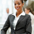 A satisfied African American business woman sitting in the offic - Stock Photo