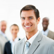 Royalty-Free Stock Photo: A handsome business man standing in front with his colleagues at