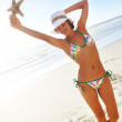 Sexy woman on the beach holding a starfish - Foto de Stock  