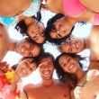 Happy friends standing a circle at the beach - Stock Photo