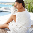 Pretty female in a bath robe sitting outdoors - Stock Photo