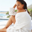 Cute female in a bath robe sitting outdoors - Stock Photo