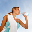 Beautiful woman drinking water during exercising - Stock Photo
