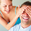 Cheerful woman covering his boyfriend's eyes to surprise him - Stock Photo