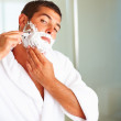 Royalty-Free Stock Photo: A young man shaving his beard