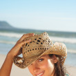 Royalty-Free Stock Photo: Beautiful woman wearing a cane hat at the beach