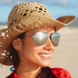 Cute female wearing sunglasses, looking away and smiling - Stock Photo