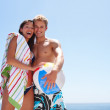 Happy couple enjoying their beach holiday - Stock Photo