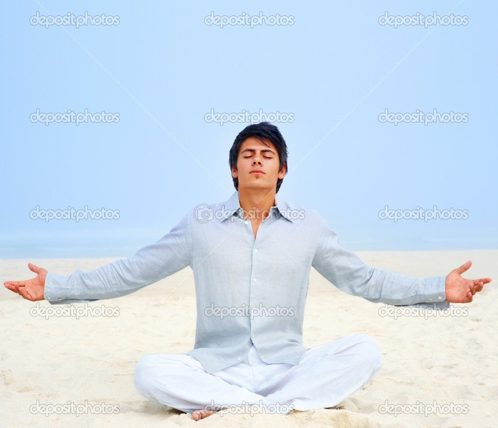 Portrait of a handsome young man meditating on the beach with his hands stretched — Stock Photo #3322833