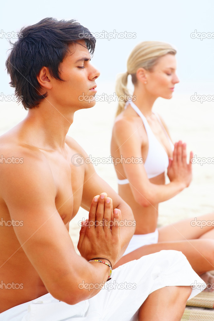 Portrait of a young man and woman sitting at the beach practicing yoga together — Stock Photo #3322929