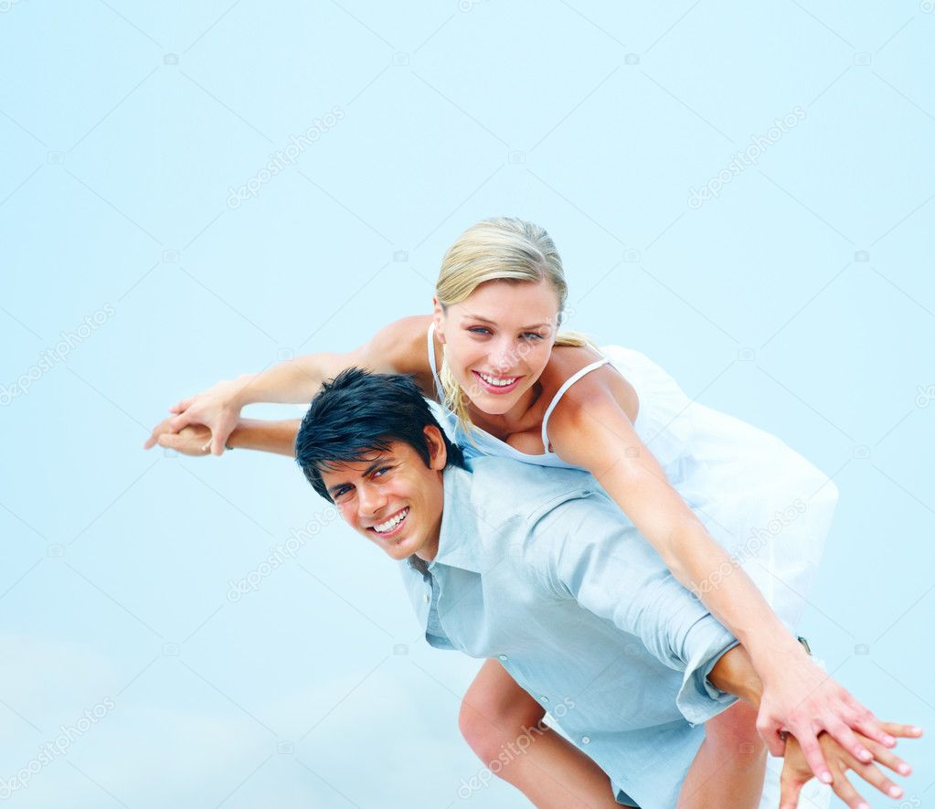 Portrait of a happy young man carrying his girlfriend on his back and stretching their hands — Stock Photo #3323008