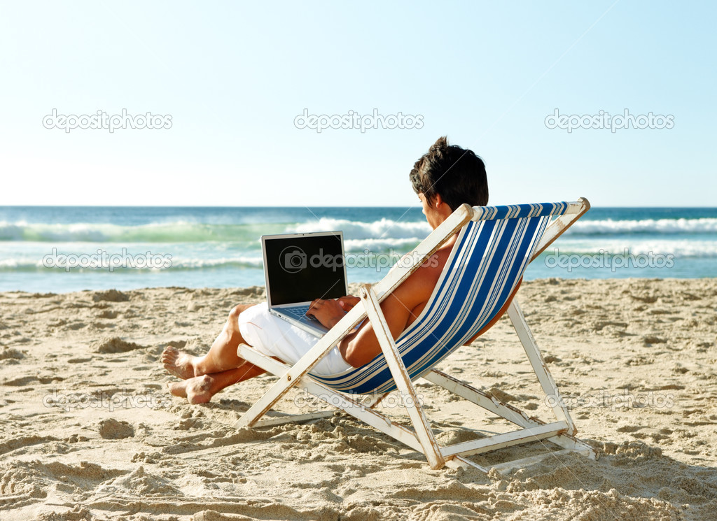 Young man sitting on a deck chair with a laptop at the beach — Stock Photo #3323866