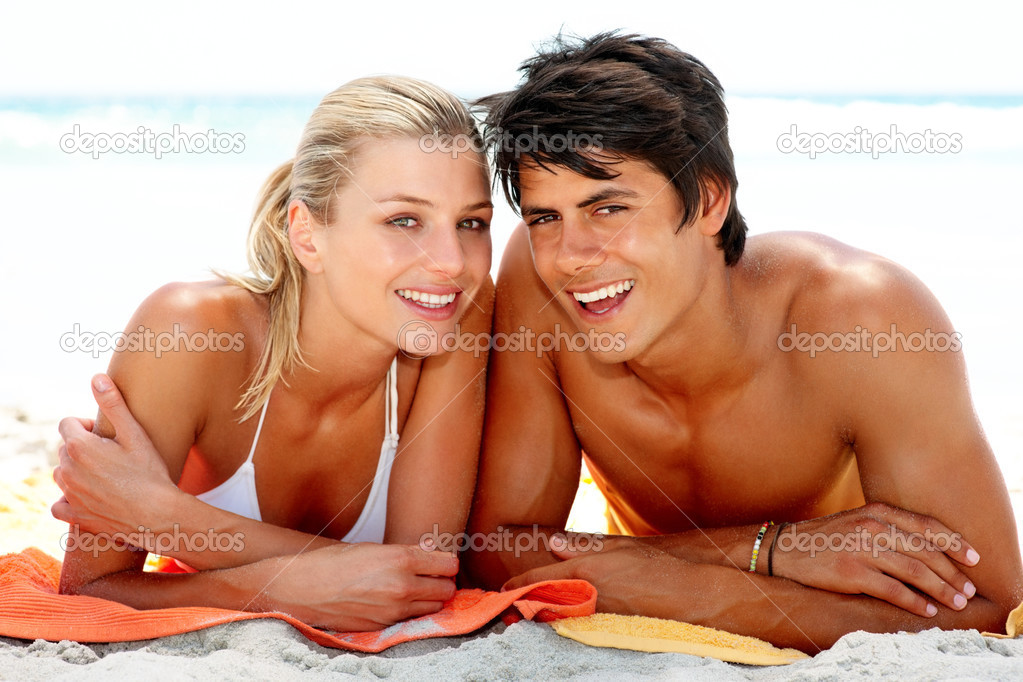 Happy young couple lying down at the beach together — Stock Photo #3323955
