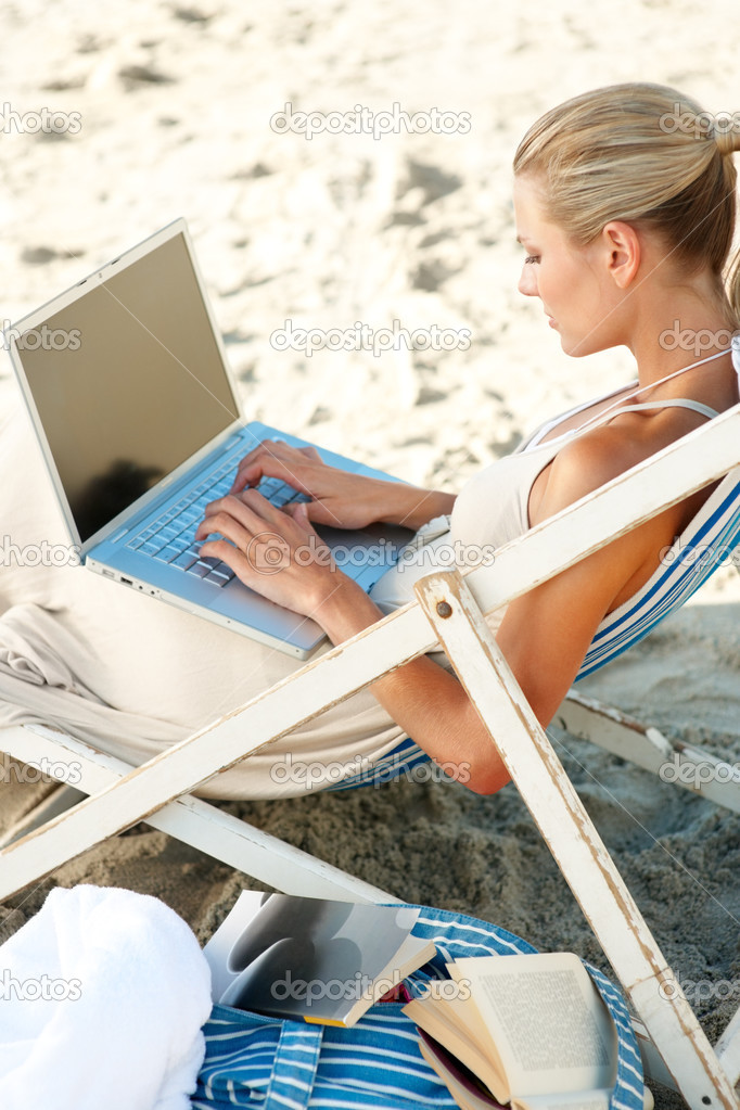 Young woman at the beach sitting on a chair while working on a laptop — Stock Photo #3324150