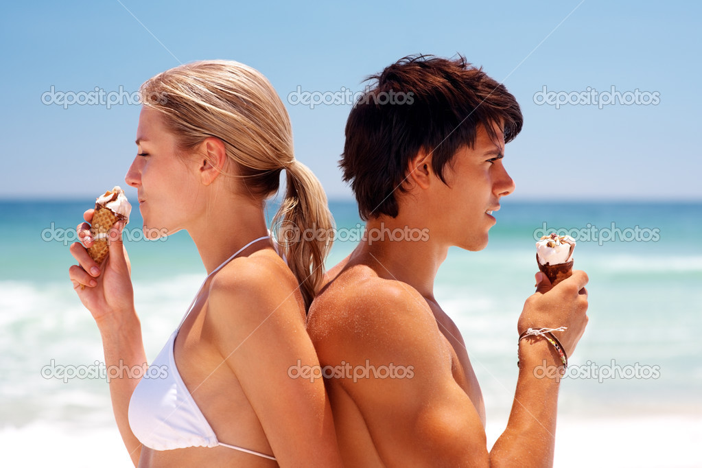 Couple at the beach eating ice cream and smiling — Stok fotoğraf #3324543