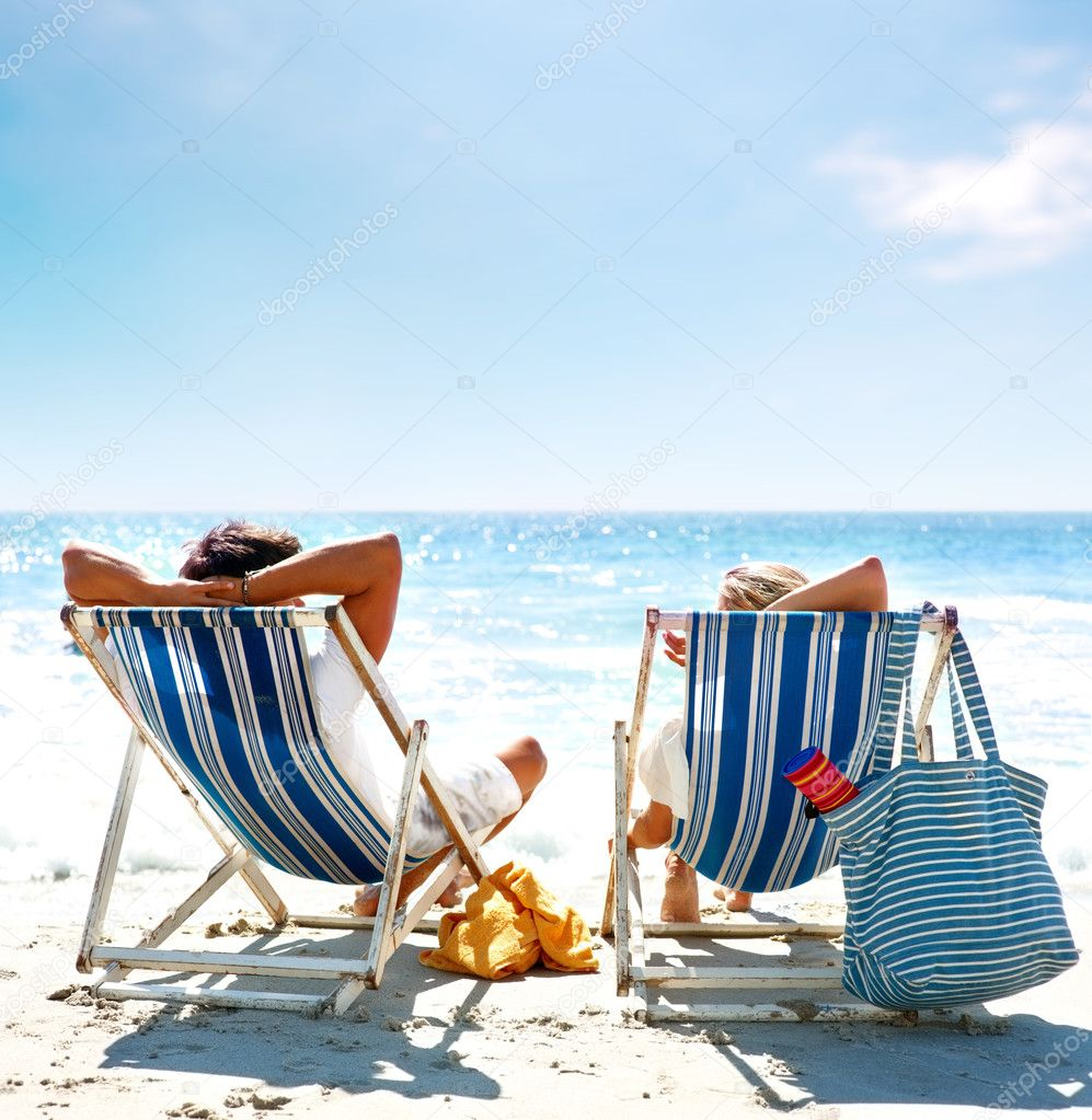 Rear view of a couple on a deck chair relaxing on the beach — Stok fotoğraf #3324602