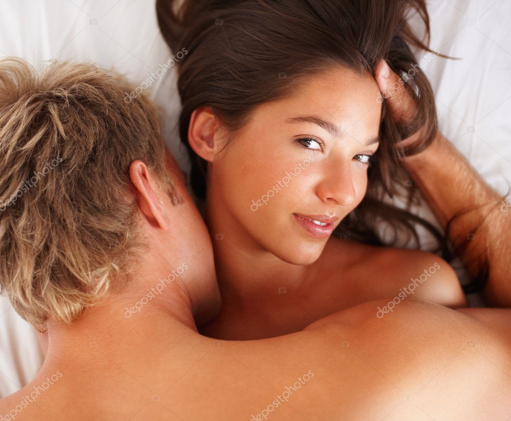 Happy young couple indulged in sexual intercourse on the bed — Stock Photo #3325877