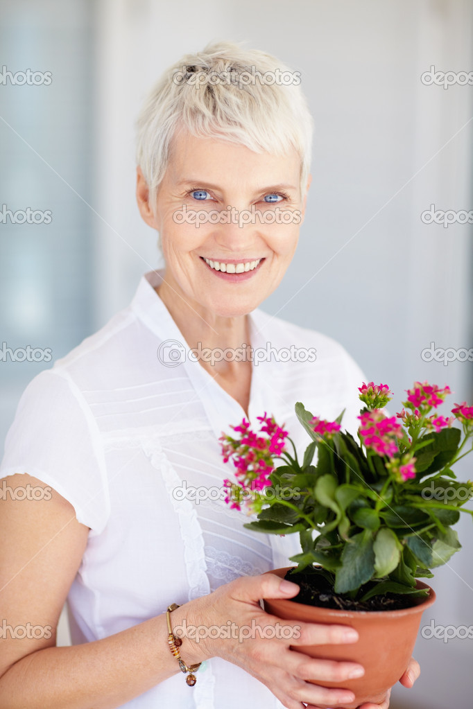 Aged woman with a pot of flowers — Stock Photo #3326544