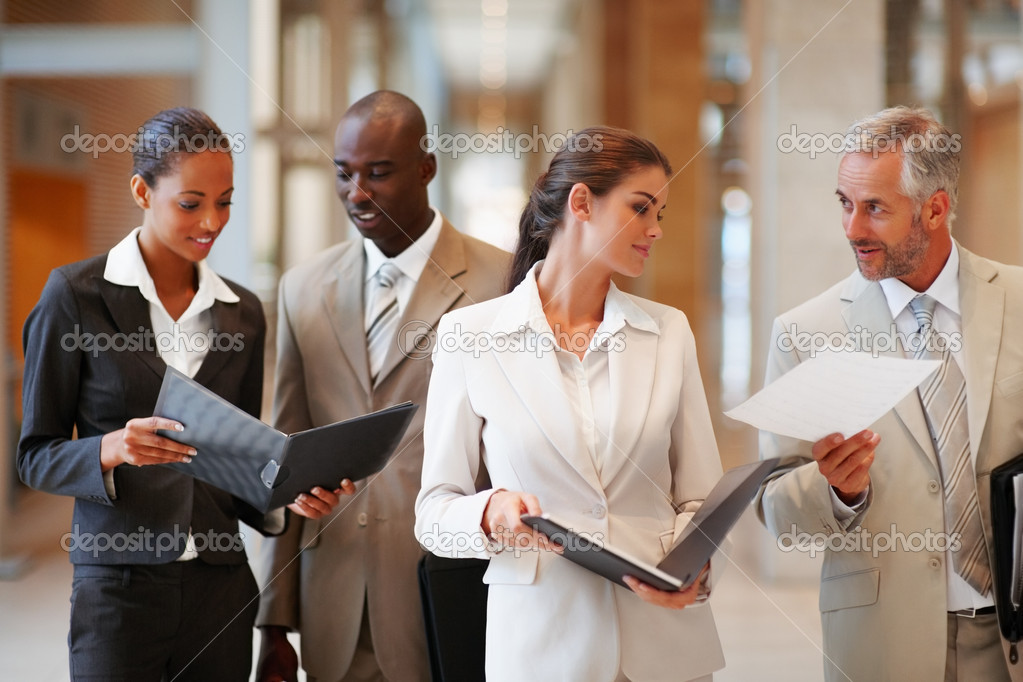 Group of business holding a file at the hallway  Stock Photo #3326910