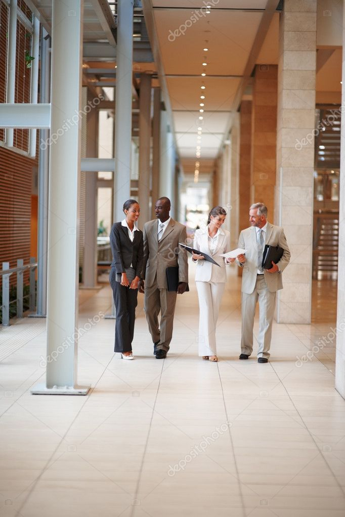 Group of four business colleagues walking through the hallway — Stock Photo #3326915