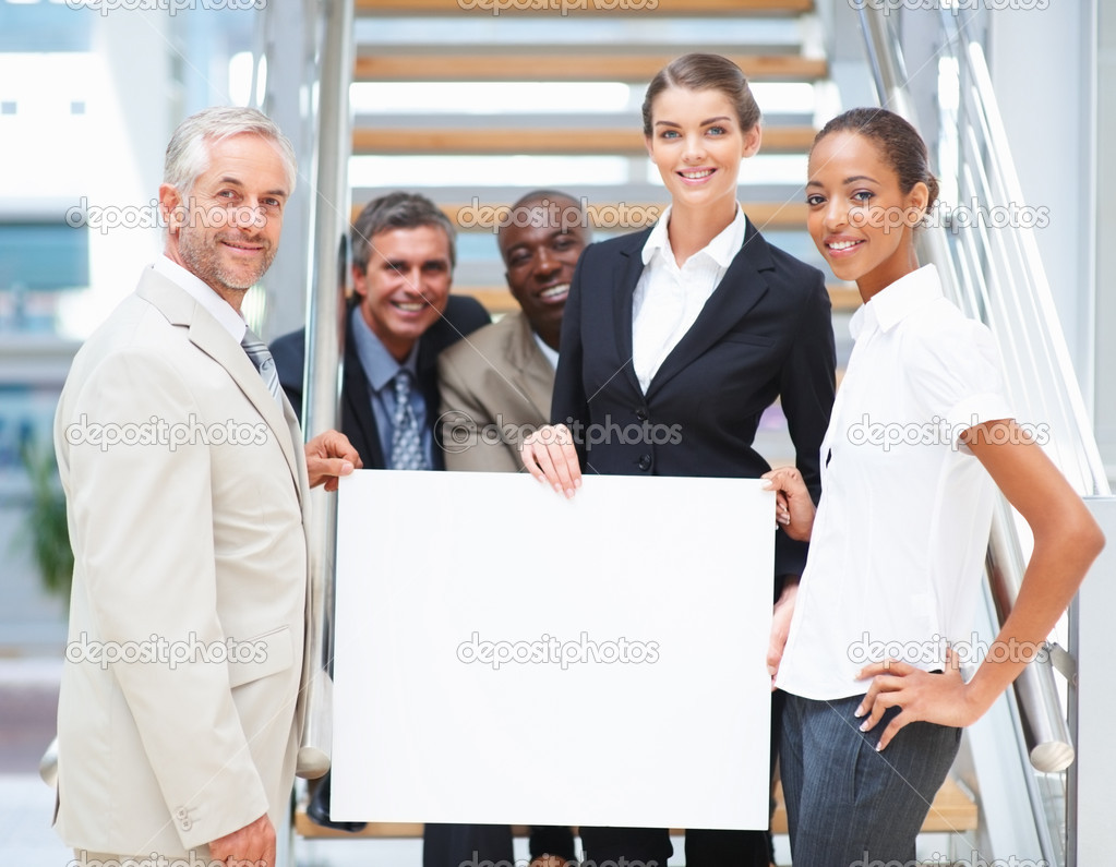Portrait of a business woman holding an empty bill board with her colleagues on the stairs — Stock Photo #3327550
