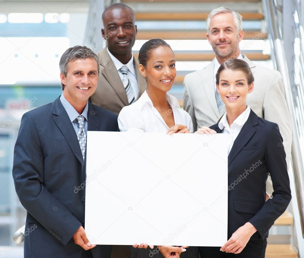 Group of business holding an empty bill board and smiling confidently — Stock Photo #3327552