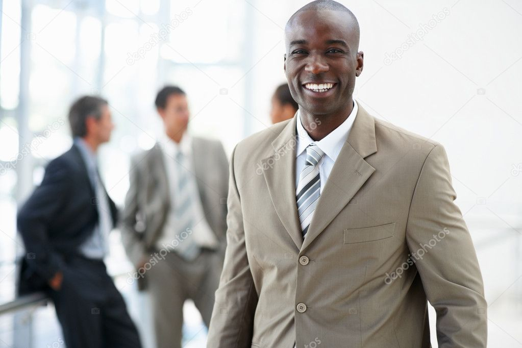 Portrait of a handsome confident African American business man smiling with his colleagues standing behind — Stock fotografie #3327576