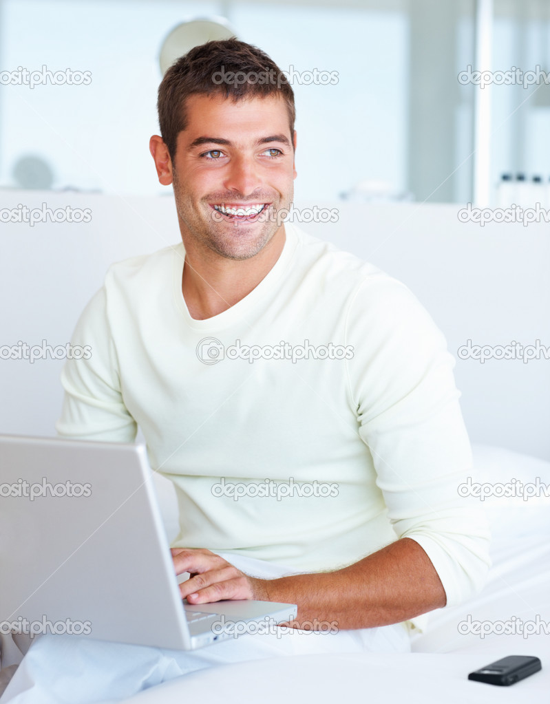 Portrait of a young man looking away while working on laptop  Stock Photo #3328729