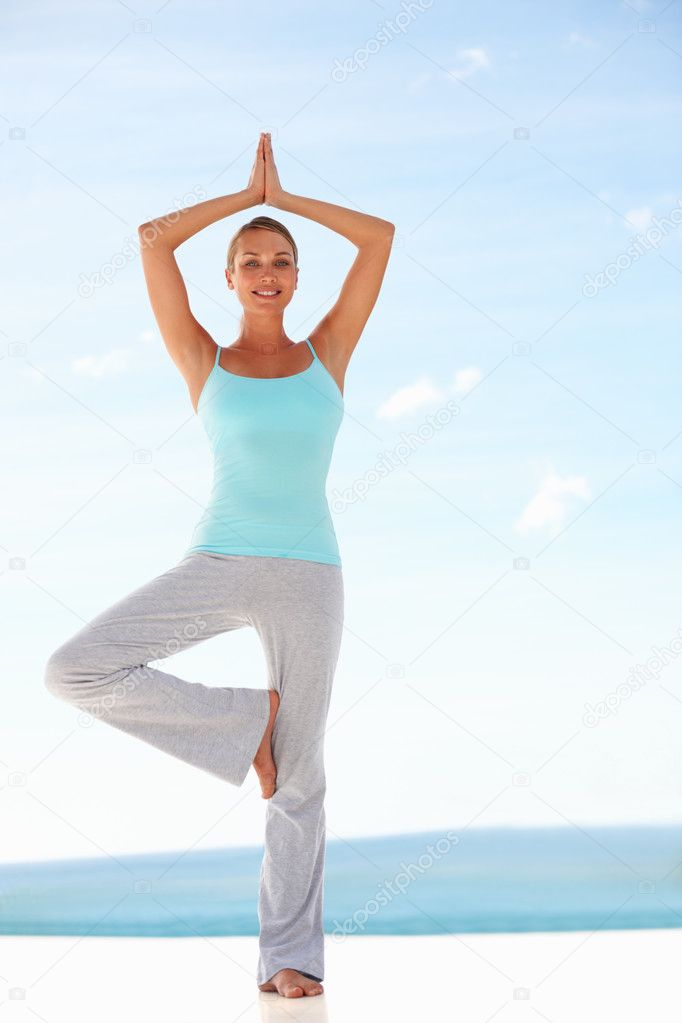 Fit woman practicing yoga with the sky at the back — Stock Photo #3329005