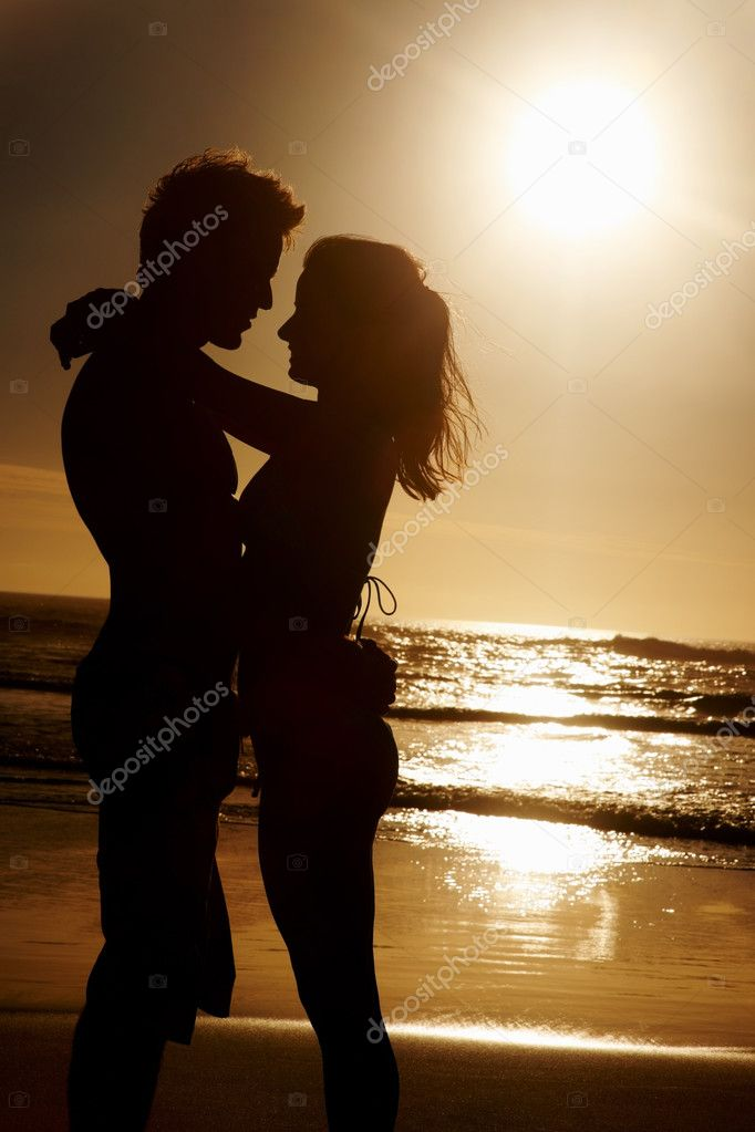 Silhouette image of a couple romancing at the beach — Stock Photo #3329277