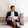 Business man sitting on the floor waiting with baggage - Foto Stock