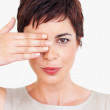 Royalty-Free Stock Photo: Young woman with hand on eye over white