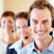 Young call centre guy with colleagues at the back - Stock Photo