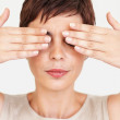 Royalty-Free Stock Photo: Cute woman with hands over her eyes on white