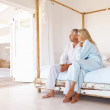 Loving senior couple sitting on the bed, looking away - Stock Photo