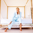 Royalty-Free Stock Photo: Portrait of a happy pretty blond sitting on a bed in her apartme