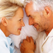 Closeup of a romantic mature couple holding hands on bed - Stock Photo