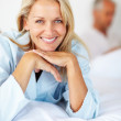 Royalty-Free Stock Photo: Beautiful mature blond lying on bed with her husband in the back