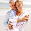 A mature couple embracing on a sunny day at the beach - Stock Photo