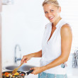 Happy mature woman cooking in the kitchen - Stock Photo