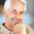 Closeup of a charming old man with hand on his chin - Stock Photo