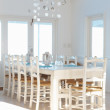 White interior with dining table and chairs and chandelier - Stock Photo