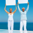 Royalty-Free Stock Photo: Senior couple at the beach holding a billboard