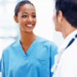 A young nurse smiling at a doctor - Stock Photo