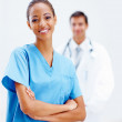 Confident nurse with a doctor at the back - Stock Photo