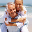 Mature couple enjoying their beach holiday - Stock Photo